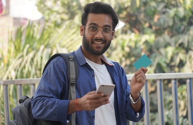 Jeune homme à lunettes shopping en ligne avec carte de crédit à l'aide d'un téléphone intelligent à la maison. extérieur.