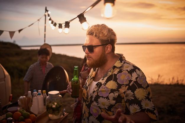 Jeune homme à lunettes tenant une bouteille de bière et dansant avec ses amis à la fête sur la plage en plein air