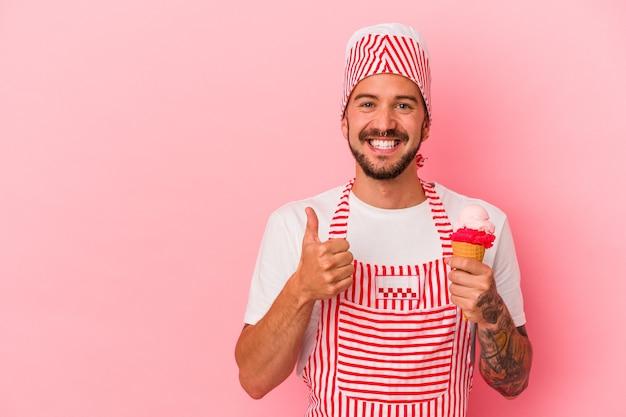 Jeune homme de machine à glaçons caucasien avec des tatouages tenant une crème glacée isolée sur fond rose souriant et levant le pouce vers le haut