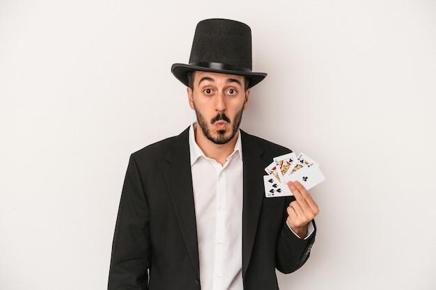 Jeune homme magicien tenant une carte magique isolée sur fond blanc hausse les épaules et ouvre les yeux confus.