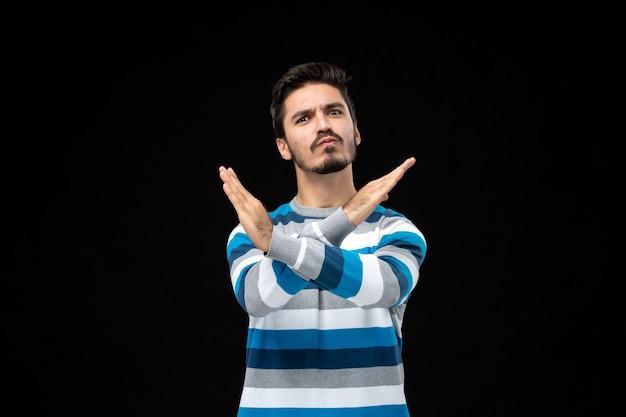Jeune homme en maillot rayé bleu croisant les mains dans un geste interdisant