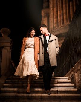 Jeune homme main dans la main avec une femme élégante heureuse et descendant sur les marches