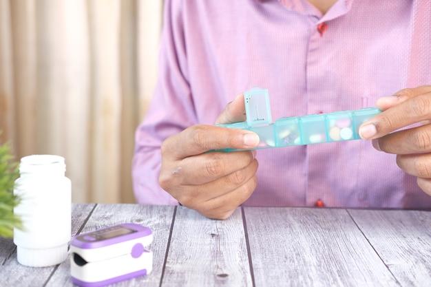 Jeune homme mains prenant des médicaments à partir d'une boîte à pilules