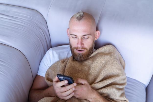 Un jeune homme à la maison sur le canapé sort avec une couverture chaude et confortable, tient un téléphone portable, lit les nouvelles