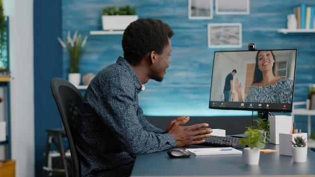 Jeune homme à la maison sur la communication d'appel vidéo en ligne, parlant avec des amis et la famille à l'aide d'une webcam sur ordinateur