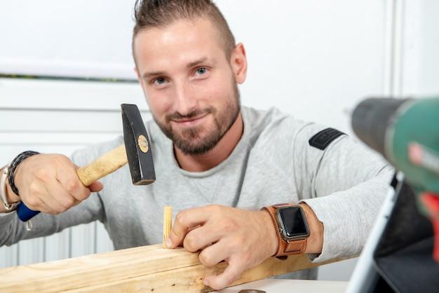 Jeune homme à la maison avec un marteau et des chevilles en bois