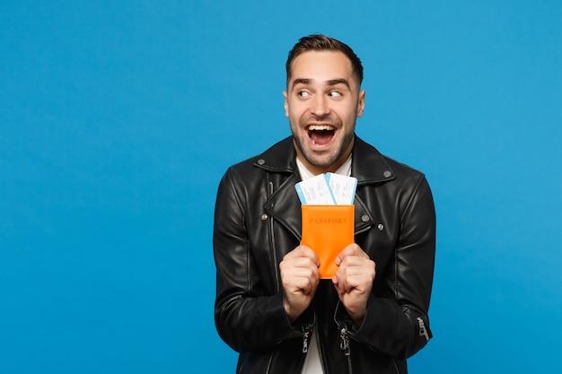 Jeune homme mal rasé heureux en t-shirt blanc veste noire tenir en main des billets de passeport isolés sur fond de mur bleu. passager voyageant à l'étranger escapade. concept de voyage de vol aérien mock up copy space