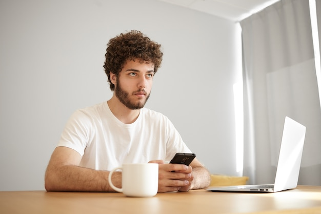 Jeune homme mal rasé à la mode avec des cheveux ondulés ayant un regard pensif tapant des sms en utilisant le wifi sur un téléphone intelligent, naviguant sur internet sur un ordinateur portable et buvant du café. les gens, le style de vie et la technologie