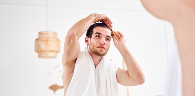 Jeune homme mal rasé se peignant les cheveux debout près du miroir dans la salle de bain