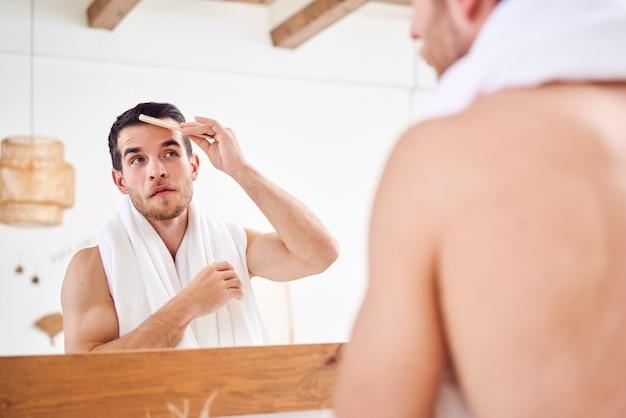 Jeune homme mal rasé se peignant les cheveux en se tenant debout avec une serviette blanche sur le cou près du miroir dans la salle de bain
