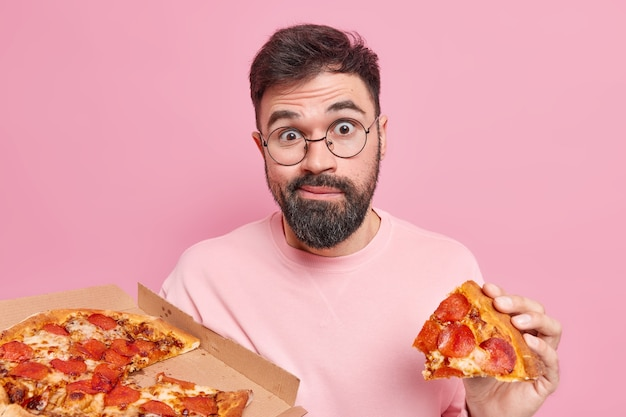 Un jeune homme mal rasé surpris et confus mange une pizza savoureuse a une dépendance à la restauration rapide apprécie une collation savoureuse dans une pizzeria semble se demander, pose contre le mur rose. concept de nutrition malsaine