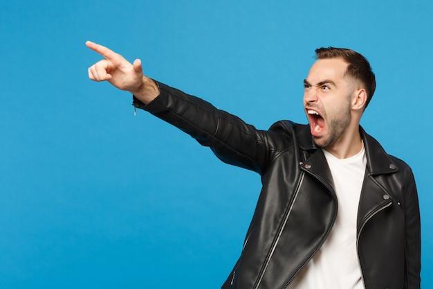 Jeune homme mal rasé triste et frustré en t-shirt blanc veste noire regardant de côté isolé sur fond de mur bleu portrait en studio. concept de mode de vie des émotions sincères des gens. maquette de l'espace de copie.