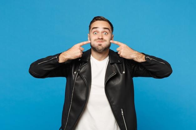 Jeune homme mal rasé en veste noire t-shirt blanc regardant la caméra pointant l'index sur les joues soufflantes isolées sur fond de mur bleu portrait en studio. concept de mode de vie des gens. maquette de l'espace de copie.