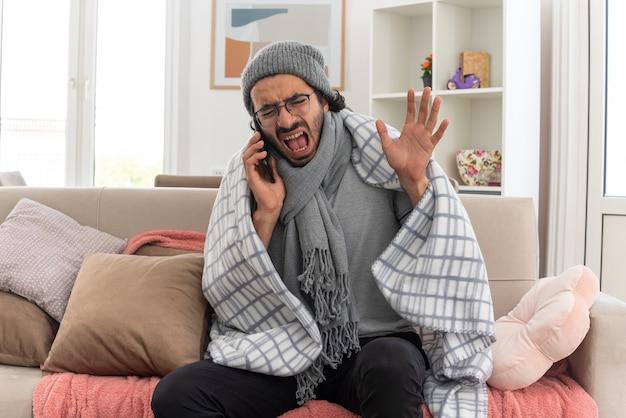 Jeune homme malade agacé dans des lunettes optiques enveloppées dans un plaid avec une écharpe autour du cou portant un chapeau d'hiver criant sur quelqu'un au téléphone levant la main et assis sur un canapé dans le salon
