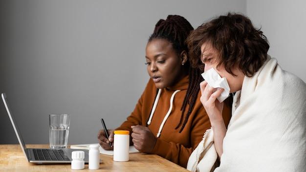 Jeune homme malade et ami ayant un appel vidéo avec un médecin