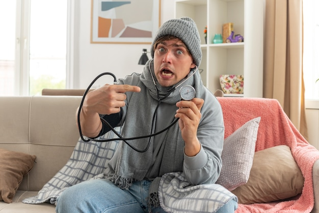 Jeune homme malade anxieux avec une écharpe autour du cou portant un chapeau d'hiver enveloppé dans un plaid mesurant sa pression et pointant sur un sphygmomanomètre assis sur un canapé dans le salon