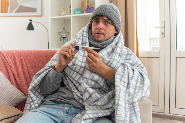 Jeune homme malade anxieux avec une écharpe autour du cou portant un chapeau d'hiver enveloppé dans un plaid tenant un thermomètre assis sur un canapé au salon