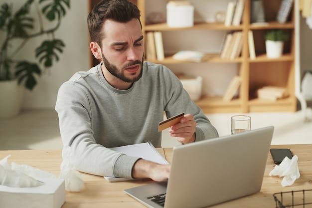 Jeune homme malade avec une carte en plastique va passer commande dans une pharmacie en ligne alors qu'il était assis par table devant un ordinateur portable dans l'environnement familial