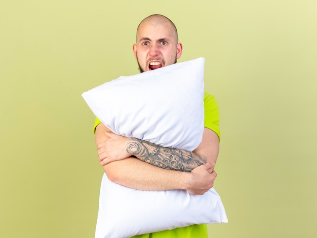 Jeune homme malade en colère tient un oreiller isolé sur un mur vert olive