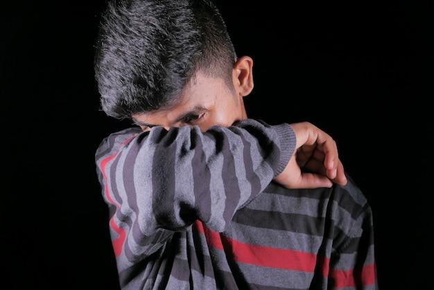 Jeune homme malade couvrant son nez et sa bouche avec bras