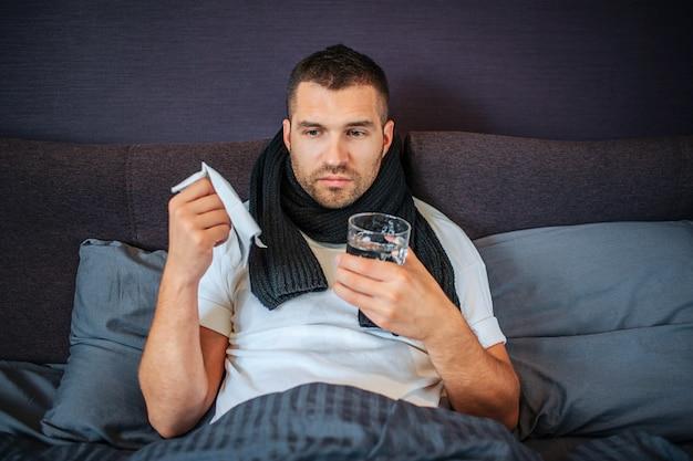 Jeune homme malade distrait est assis sur le lit avec une partie basse du corps couverte. il tient une serviette blanche et du verre sur l'eau. il y a aussi un foulard autour du cou.