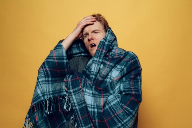 Jeune homme malade enveloppé dans une toux plaid
