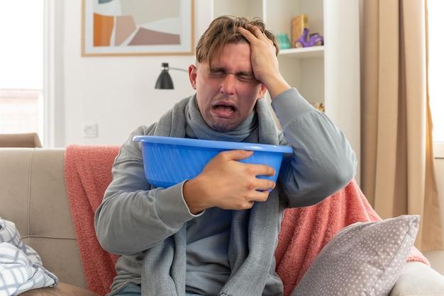 Jeune homme malade avec un foulard autour du cou mettant la main sur son front et tenant un seau assis sur un canapé dans le salon