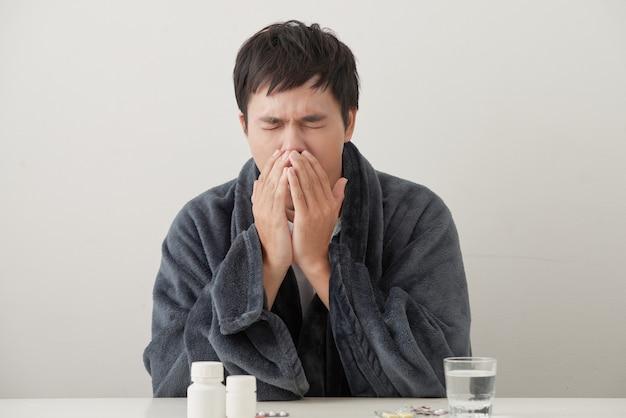 Jeune homme malade et malade dans un canapé tenant un tissu nettoyant le nez morveux ayant une température se sentant mal infecté par le virus de la grippe hivernale dans le concept de soins de santé de la grippe et de la grippe.
