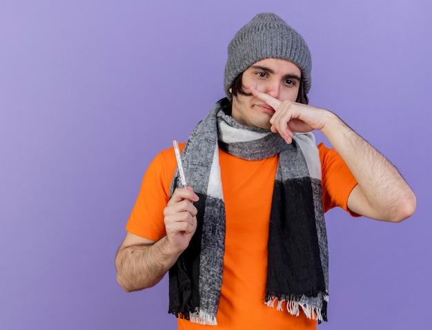 Jeune homme malade portant un chapeau d'hiver avec écharpe tenant un thermomètre essuyant le nez avec le doigt isolé sur violet