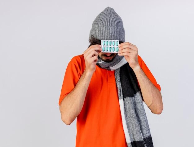 Jeune homme malade de race blanche portant des lunettes chapeau d'hiver et écharpe tenant pack de capsules devant les yeux isolé sur fond blanc avec espace copie
