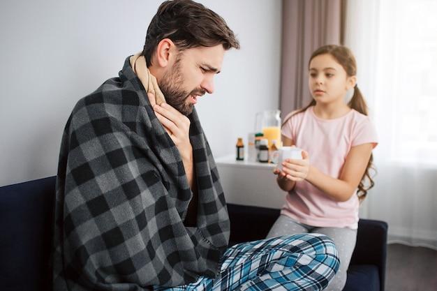 Jeune homme malade s'asseoir et couvert de couverture. il tient les mains sur la gorge. sérieuse petite fille le regarde et tient une tasse blanche.