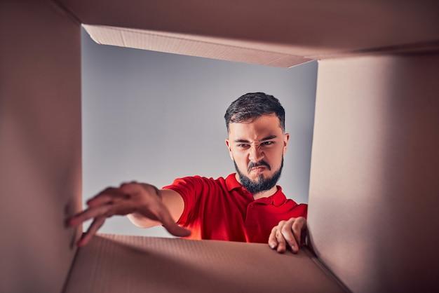 Un jeune homme maléfique déçu regarde un cadeau à l'intérieur d'une boîte en carton.
