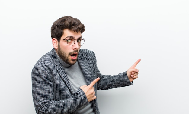 Jeune homme manager se sentant choqué et surpris, pointant pour copier l'espace sur le côté avec un regard étonné et bouche ouverte contre le mur blanc