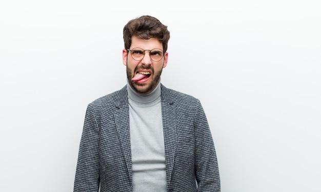 Jeune homme manager se sentant dégoûté et irrité, tirant la langue, n'aimant pas quelque chose de méchant et dégueu contre un mur blanc