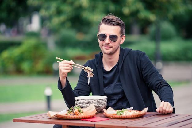 Jeune homme mangeant des nouilles à emporter dans la rue