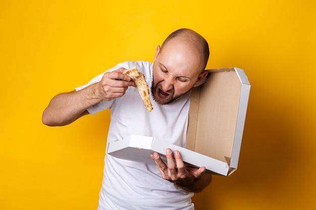 Jeune homme mangeant une pizza fraîche chaude avec un emballage sur une surface jaune.