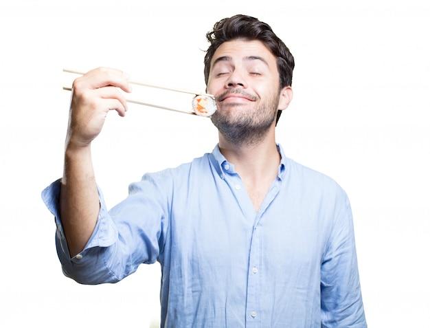 Jeune homme manger des sushis sur fond blanc