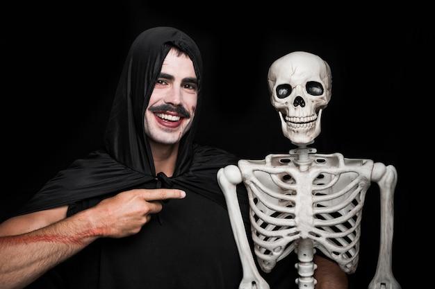 Jeune homme en manteau noir pointant vers le squelette