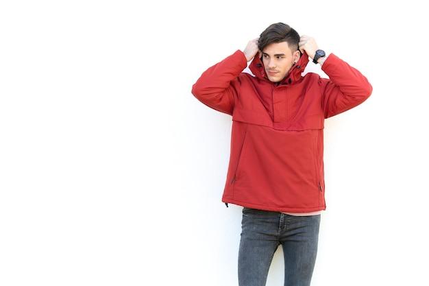 Jeune homme en manteau rouge sur mur blanc