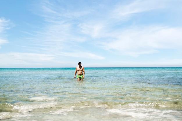 Un jeune homme marchant dans l'eau de mer pour nager pendant les vacances d'été