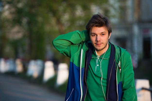 Jeune homme marchant dans la ville en écoutant de la musique avec des écouteurs, regarde la caméra et souriant. photo en gros plan.