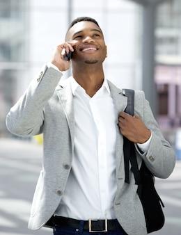Jeune homme marchant et parler au téléphone mobile