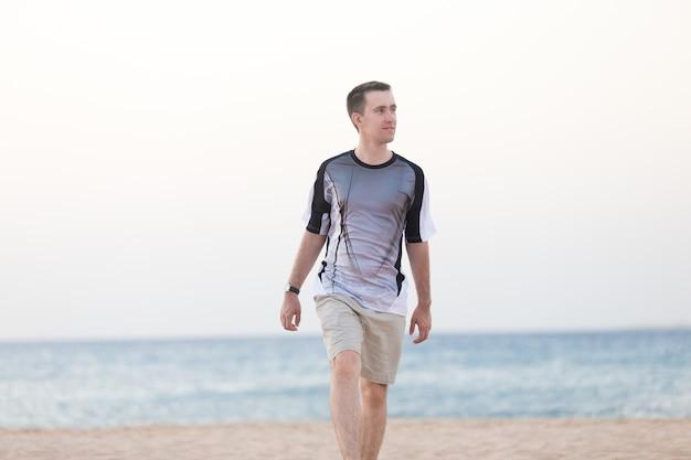 Jeune homme marchant sur la plage