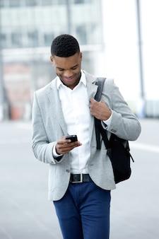 Jeune homme marchant et regardant le téléphone mobile