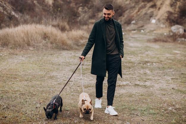 Jeune homme marchant son bouledogue français dans le parc