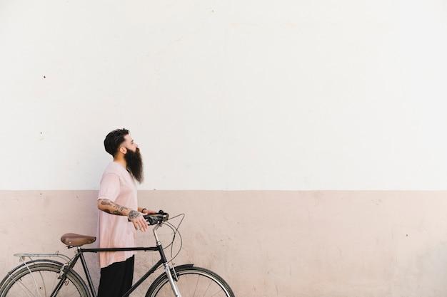 Jeune homme marchant avec vélo contre mur peint
