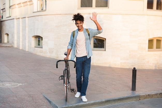 Jeune homme marchant à vélo à l'extérieur dans la rue en agitant