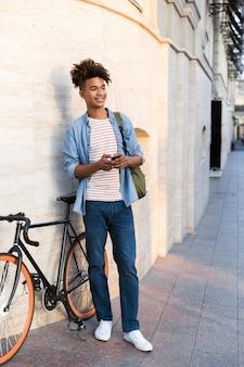Jeune homme marchant avec vélo à l'extérieur dans la rue à l'aide de téléphone mobile
