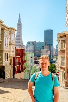Un jeune homme marche le long d'une belle rue avec vue sur la transamerica tower à san francisco