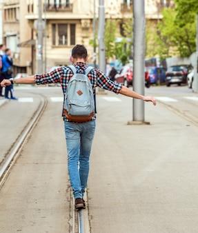 Jeune homme, marche, tram, rails
